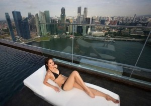 A model lies on a bed in the infinity pool of the Skypark that tops the Marina Bay Sands hotel towers in Singapore June 24, 2010. The Sands Skypark, which opened to the public on Thursday, features a 150-metre-long infinity pool overlooking Singapore's city skyline and Marina Bay, a public observation deck and a restaurant run by a celebrity chef. REUTERS/Vivek Prakash (SINGAPORE - Tags: BUSINESS SOCIETY CITYSCAPE TRAVEL)